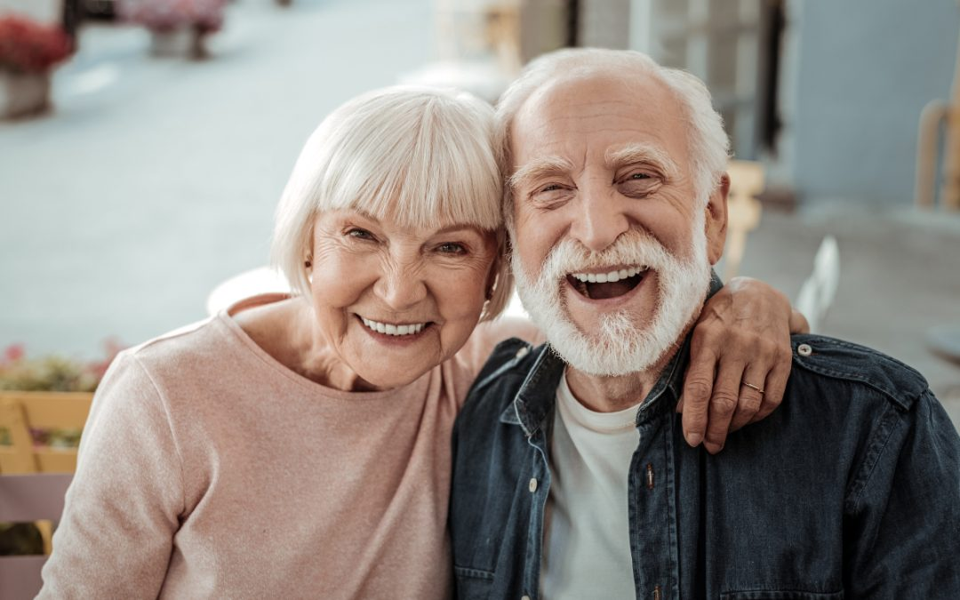 elderly couple smiling with bright, white teeth